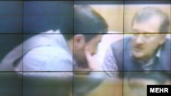 فاضل لاریجانی (راست) در گفتوگو با سعید مرتضوی. پخش فیلم دیدار آنها در مجلس جنجال تازهای را در حکومت جمهوری اسلامی رقم زد.