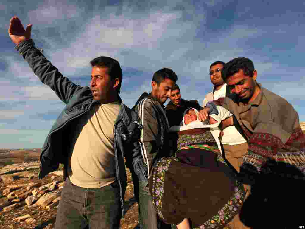 Palestinian men carry a woman who fainted after a confrontation with settlers and Israeli soldiers in the West Bank. - Photo by epa