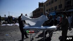 Afghan volunteers carry the bodies of victims at the scene of a suicide attack that targeted crowds of minority Shiite Hazaras during a demonstration at the in Kabul on July 23.