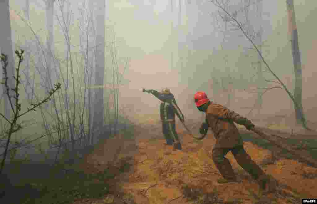 Ukrainian firefighters battle flames near the village of Rahivka on 10 April.The fires began on April 3 in the western part of the uninhabited exclusion zone before spreading to nearby forests.