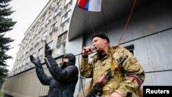 Ռուսամետ ցուցարարը Կալաշնիկովի ինքնաձիգը ձեռքում ելույթ է ունենում Լուգանսկի անվտանգության ծառայության վարչության մուտքի մոտ: 11֊ը ապրիի, 2014թ.