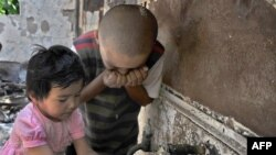 Children drinking water from a damaged building in Osh following the June violence.