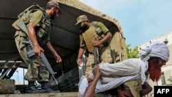 Ushtarët pakistanezë e tërheqin një militant të dyshuar, i cili ishte arrestuar gjatë një operacioni të armatës së Pakistanit në rajonin Bara