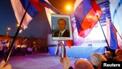 Женщины держат в руках потрет президента России Владимира Путина и российские флаги после аннексии Крыма Россией. Симферополь, 21 марта 2014 года.