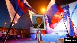 Люди в центре Симферополя держат российские флаги и портрет президента России Владимира Путина. 21 марта 2014 года.