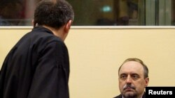 Goran Hadzic (right) makes his initial appearance to stand trial for alleged crimes against humanity before the International Criminal Tribunal for the former Yugoslavia (ICTY) in The Hague on July 25.