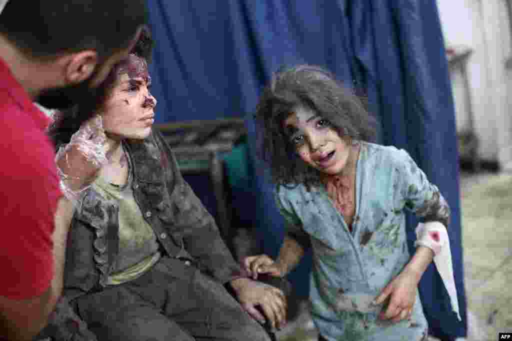 A Syrian medical worker treats a young girl as another looks on at a makeshift hospital in the rebel-held town of Douma near Damascus after reported air strikes by Syrian government forces. (AFP/Abd Doumany)