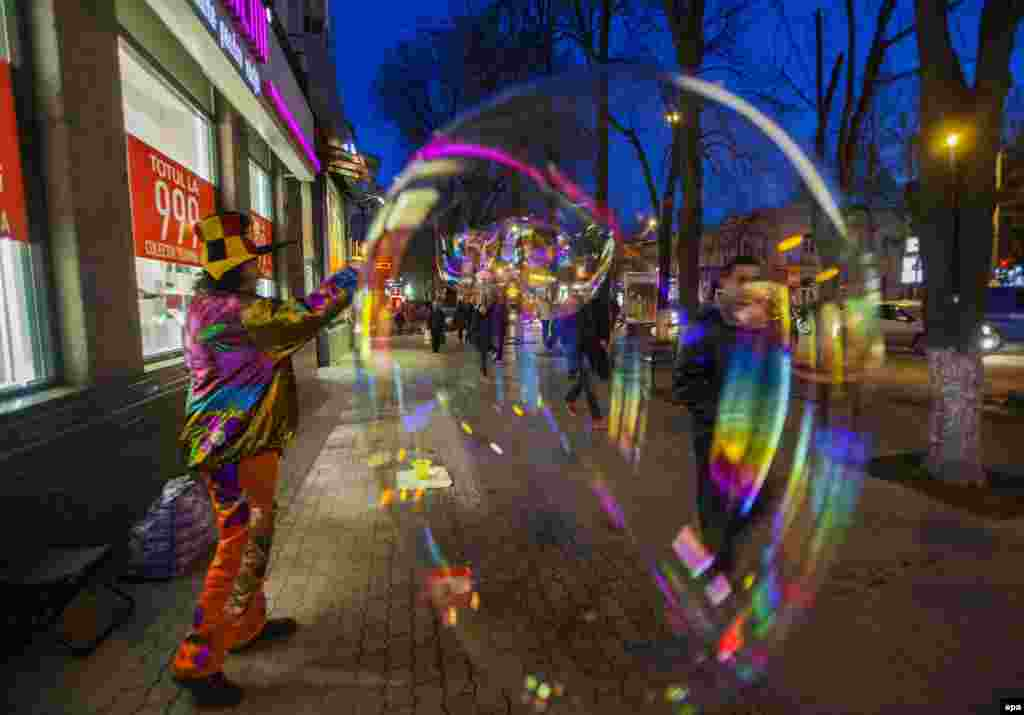 A man dressed as a clown makes huge soap bubbles in downtown Chisinau as part of the Martisor festival, which celebrates the start of spring on March 1. (epa/Dumitru Doru)