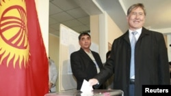Алмазбек Атамбаев бросает бюллетень на избирательном участке президентских выборов. Бишкек, 30 октября 2011 года.