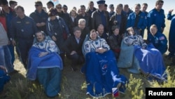 Canadian Chris Hadfield, Russian Roman Romanenko, and American Tom Marshburn rest after leaving the Russian Soyuz space capsule following its landing in Kazakhstan on May 15.