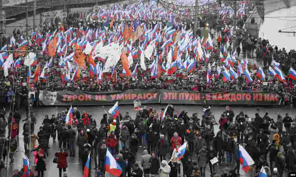 "Marchers hold up a poster with Boris Nemtsov's portrait saying: ""Heroes do not die. These bullets -- in each of us."""