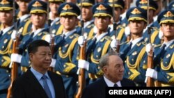 Kazakh President Nursultan Nazarbayev (R) reviews a military honor guard with Chinese President Xi Jinping at a welcome ceremony outside the Great Hall of the People in Beijing on June 7.