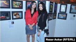 سارا ويما امام لوحاتهما الفوتوغرافية
