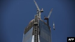 The 408-foot spire is hoisted up onto a temporary platform on the top of One World Trade Center in New York,