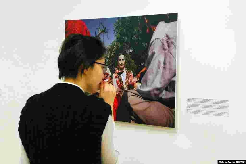 Посетительница выставки Франка Вожеля перед фотографией, на которой изображено, как семья бишноя Ганги Рама чтит его память. Ганга Рам погиб от пули браконьеров, защищая газель. За этот поступок он был награжден высшей наградой Индии для защитников природы.