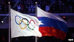 Russia -- The Olympic flag (L) and the Russian flag during the Closing Ceremony of the Sochi 2014 Olympic Games in the Fisht Olympic Stadium in Sochi, February 23, 2014