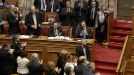 Prime Minister Antonis Samaras (blue tie) applauds with lawmakers after a vote at the parliament in Athens, on November 8.