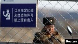 Түндүк Корея: Ялуцзян дарыясынын ортосундагы чек ара бекетинде турган аскер.