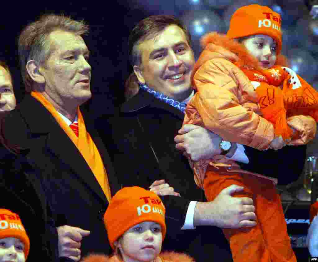 Ukrainian President-elect Viktor Yushchenko (left) and Georgian President Mikheil Saakashvili (right) greet residents of the Ukranian capital for the New Year on January 1, 2005 at Independence Square in Kyiv.