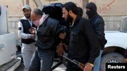 Сириялык козголоңчулардын исламчыл Жабхат ан - Нусра тобунун согушчандары туткунду машинеге салганы жатышат. Рагга провинциясы. 14-март 2013