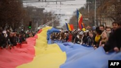 Участники протеста развернули флаг Молдовы на акции против нарушений на выборах президента. Кишинев, 14 ноября 2016 года