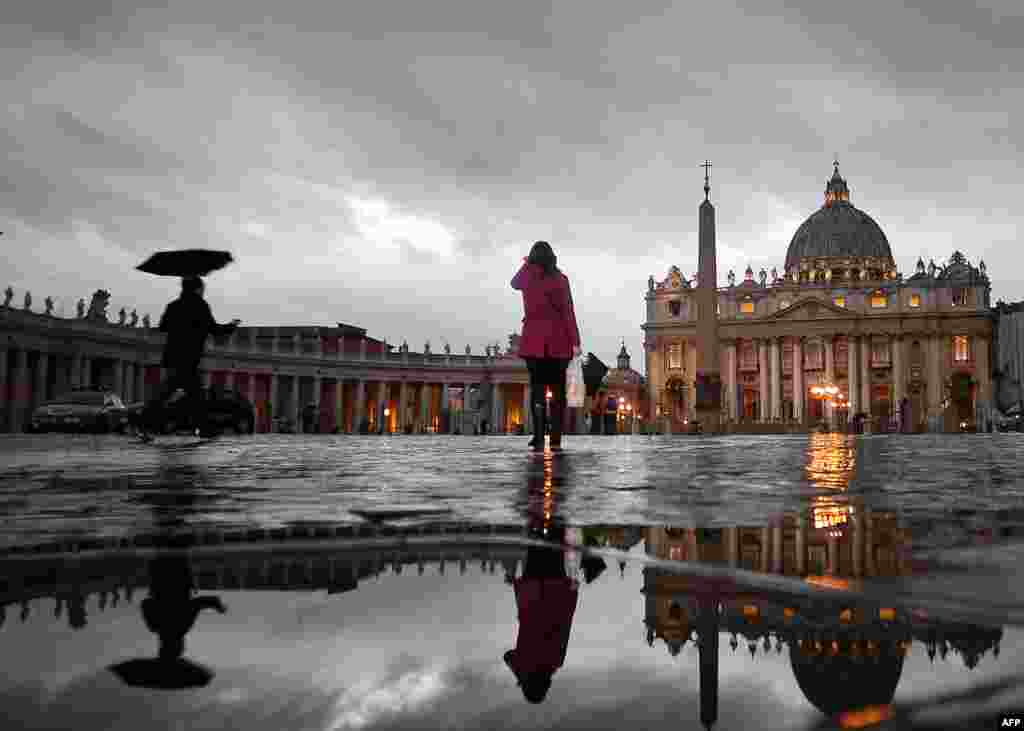 People walk in St. Peter's Square. The Vatican announced that Roman Catholic cardinals would start their conclave to elect a successor to Pope Benedict XVI on March 12. (AFP/Filippo Monteforte)