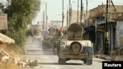 Peshmerga forces ride on military vehicles in the town of Bashiqa after it was recaptured from the Islamic State, east of Mosul, Iraq, on November 9.
