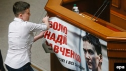 Savchenko removes a poster with her portrait as she attends her first session in the parliament in Kyiv on May 31.