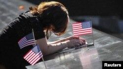 أميركية تنحني أمام إسم زوجها المنقوش في نصب لتخليد ضحايا هجمات 11 أيلول في نيويورك