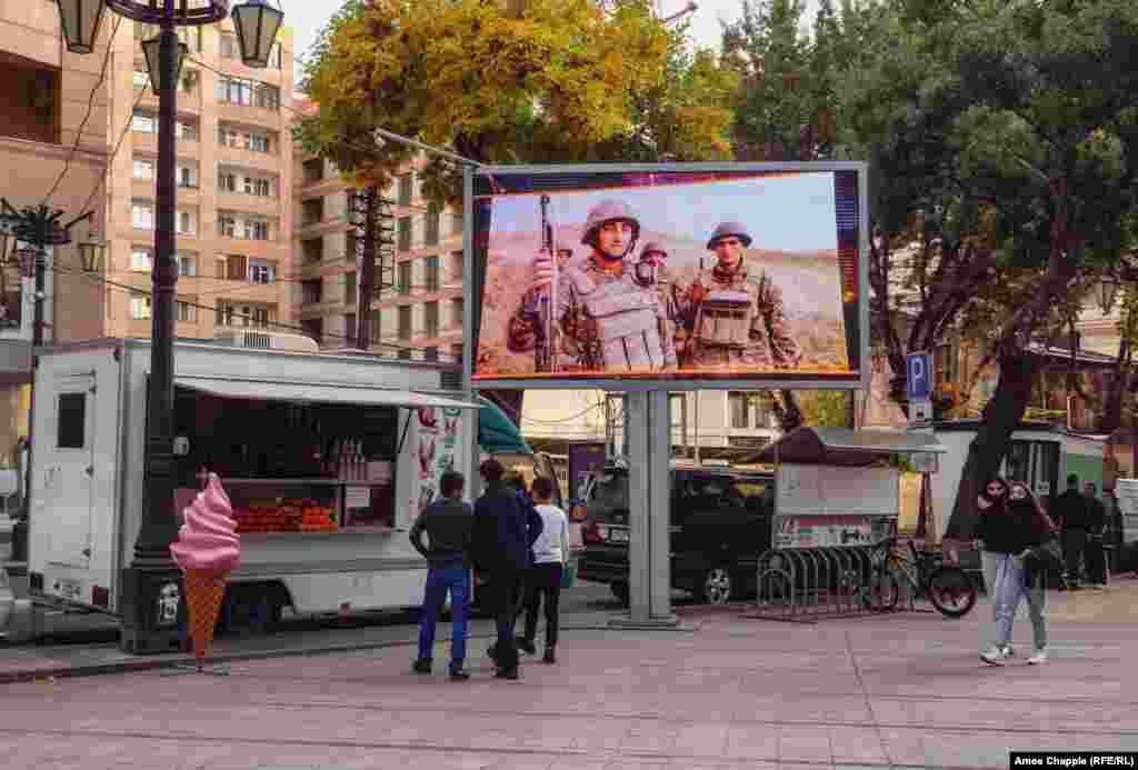 Кадры с военными, транслируемые на большом экране в центре Еревана, 28 октября 2020 года