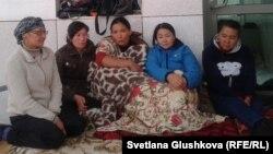 """Жители бывшего дачного массива, чьи дома попадают под снос из-за изъятия земель """"под госнужды"""", сидят на крыльце здания Дома правительства. Астана, 27 июля 2014 года."""