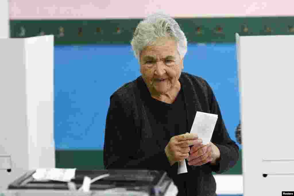 Жінка готується віддати свій голос за одного з кандидатів на посаду міського голови Струміци, що у Македонії