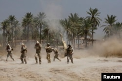 """""""Ислам мемлекеті"""" содырларымен атысып жатқан Ирак армиясы жауынгерлері. Бағдат маңы, 30 маусым 2014 жыл. (Көрнекі сурет)"""