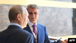 Russian state bank chief German Gref (right) with President Vladimir Putin in Crimea in 2014.
