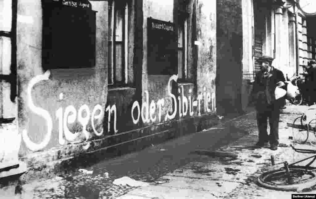 "A German man looks at the phrase ""Victory or Siberia"" painted on a building. For many who remained, the grim maxim proved accurate. Millions of Germans were shipped east by the Soviets and some 357,000 died in labor camps or secret police prisons."