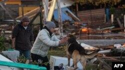 Жер сілкінісінен қираған үй орнында жүрген адамдар мен ит. Чили, 17 қыркүйек 2015 жыл. (Көрнекі сурет.)
