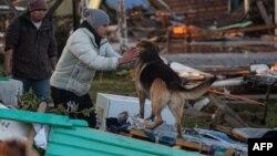 Люди, спасшиеся от землетрясения и цунами в Чили 17 сентября 2015 го, собирают остатки имущества на развалинах домов