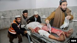 A man injured in a bomb blast at an Islamic center in Peshawar is rushed to a local hospital on January 16.