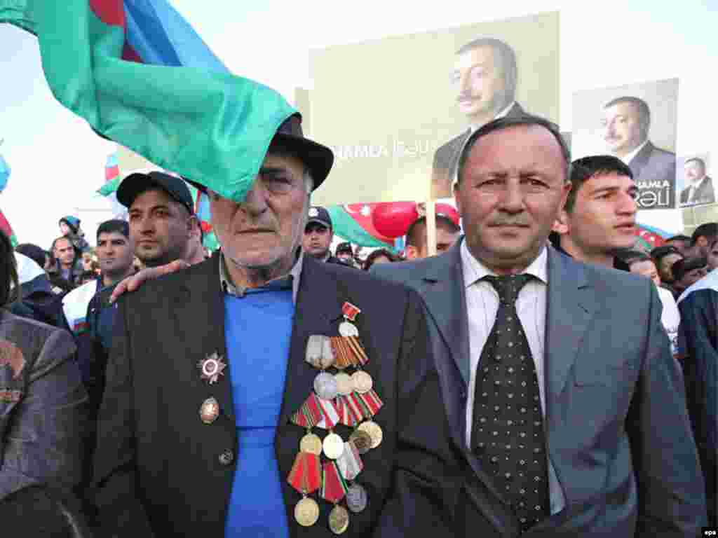 Caption: epa01519140 Azeri people stand in front of pre-electoral posters of candidate and present President of Azerbaidan Ilkham Aliyev during a rally supporting his candidacy in the upcoming presidential elections in Sumgait, some 30km from Baku, Azerbaijan, 13 October 2008.