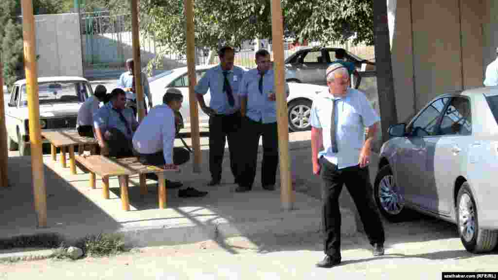 """Aşgabadyň """"Awtokombinat"""" duralgasyndaky awtobus sürüjileri günorta arakesmesinde dynç alýarlar."""