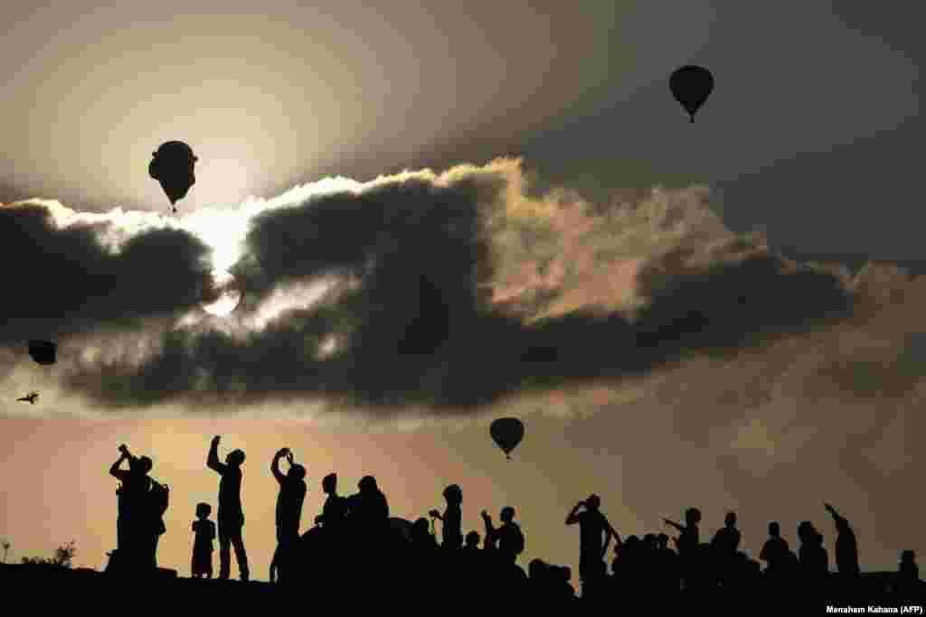 Israelis watch and take photos of hot air balloons flying during the Gilboa Hot Air Balloon Festival near Kibbutz Ein Harod in northern Israel's Jezreel Valley. (AFP/Menahem Kahana)