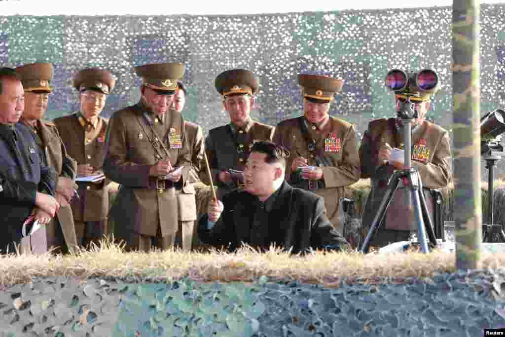 Військові, що оточують присутнього на ракетних навчаннях Кім Чен Ина, тримають блокноти і ручки, щоб записувати всі вказівки від верховного лідера. Листопад 2015 року