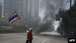 A ''Red Shirt'' anti-governement protester waves a national flag during clashes with soldiers in Bangkok on May 14.