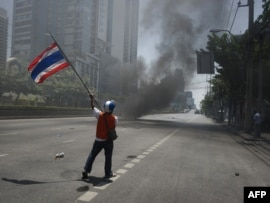 An antigovernement protester waves a national flag during clashes in Bangkok on May 14.
