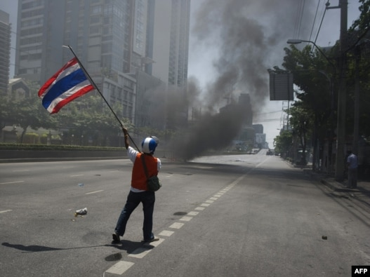 A 'Red Shirt' anti-governement protester waves a national flag during clashes with soldiers in Bangkok on May 14.