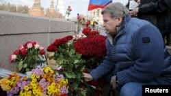 A man lays flowers on the bridge in Moscow where Russian politician Boris Nemtsov was killed.