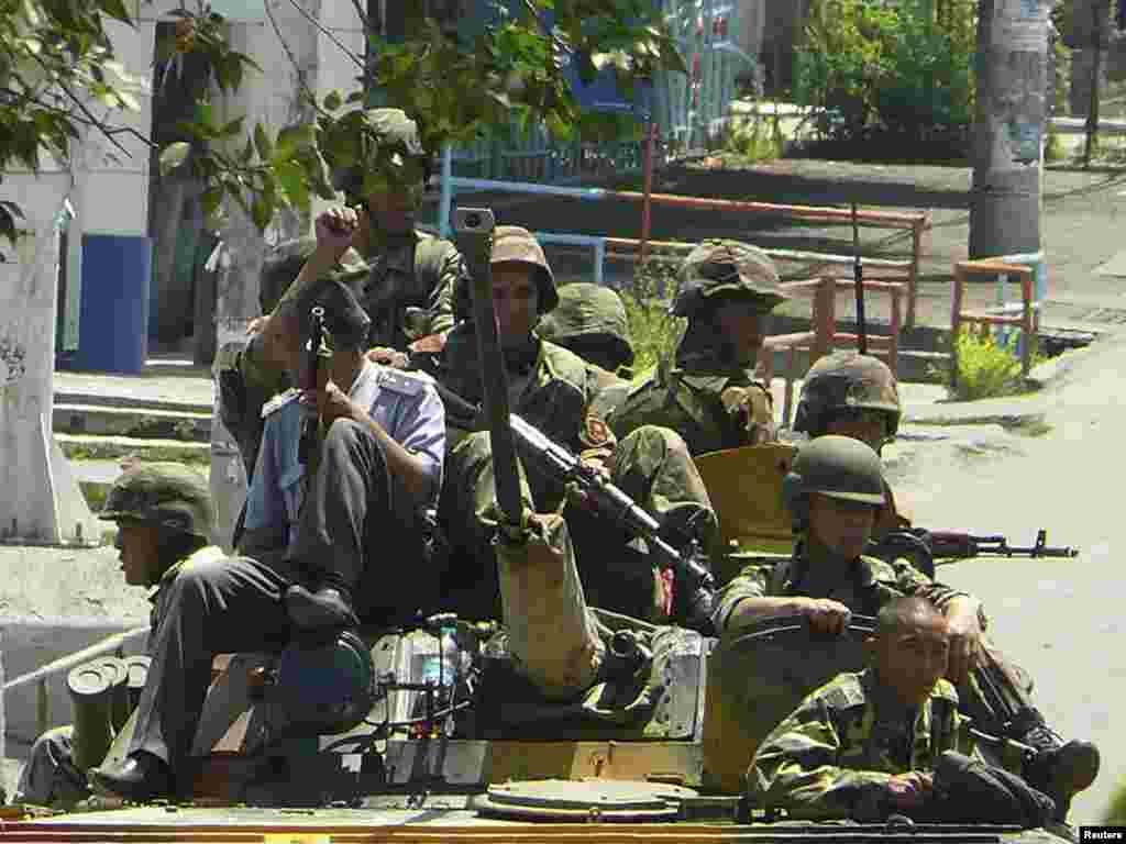 Танктын үстүндө бараткан жоокерлер жана милиция кызматкери. 11-июнь, 2010-жыл.