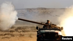 An anti-Qaddafi fighter fires a cannon during a battle with Qaddafi loyalists near Sirte.