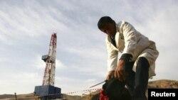 Мужчина забивает барана на фоне буровой установки на месторождении газа Сарыкамыш. Таджикистан, 7 декабря 2010 года.
