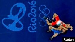 Алмат Кебіспаев (көк формада) Рио олимпиадасында ирандық балуанмен күресіп жатқан сәт. 14 тамыз 2016 жыл.